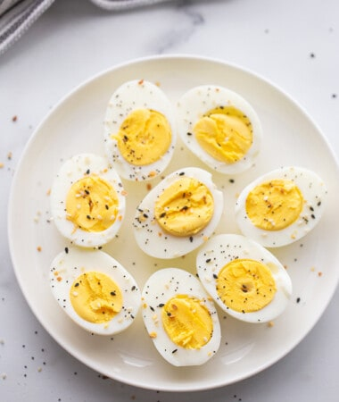 Top view of 4 hard boiled eggs cut in half on a white plate with Everything Bagel Seasoning