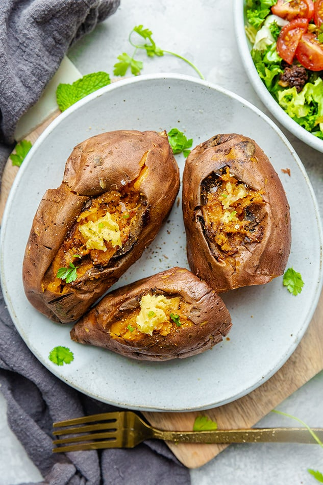 Three Instant Pot sweet potatoes with vegan butter and parsley on a white plate