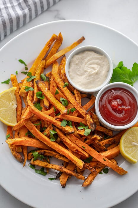 Top view of air fryer sweet potato fries on a white plate with ketchup and aioli