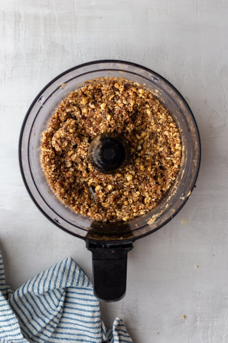 Top view of blended ingredients to make apple pie energy bites in a food processor