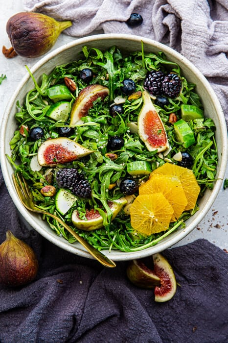 Top view of an arugula salad in a white bowl with figs + citrus