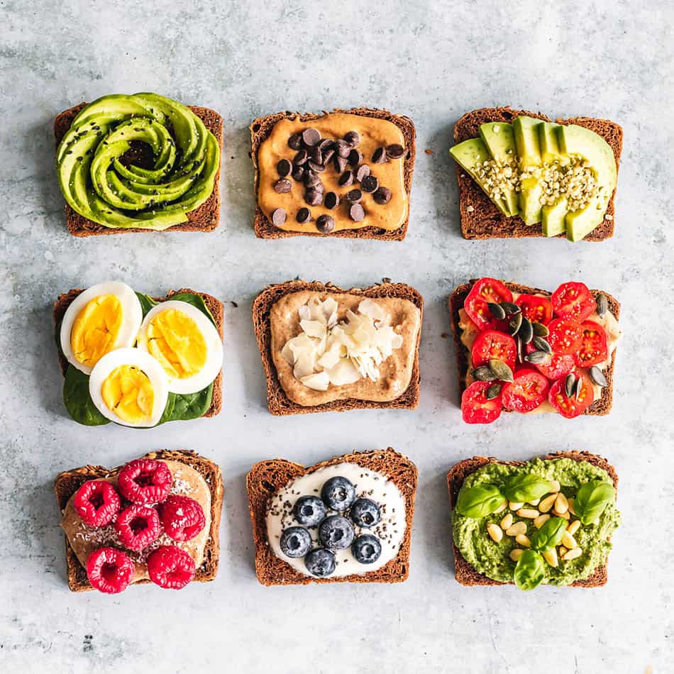 Top view of 9 slices of avocado toasts on a grey background