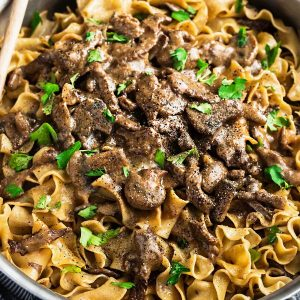 one pan beef stroganoff with mushrooms in a creamy gravy over cooked noodles