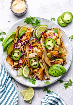 Top view of 3 cauliflower tacos in a white bowl with creamy sauce