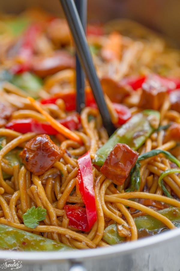 Close up of delicious Chicken Lo Mein noodles with snow peas, red bell peppers and juicy chicken in a large silver skillet.