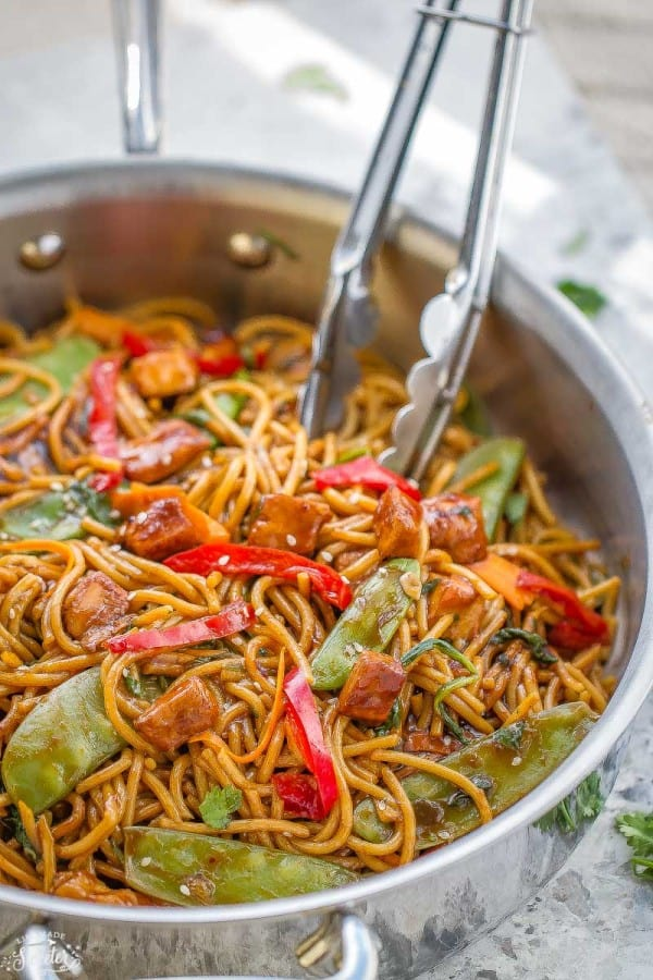 Easy Chicken Lo Mein recipe with carrots, red bell peppers and snow peas with a pair of silver tongs inside of a large silver skillet.