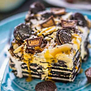 Side view of one slice of chocolate icebox cake on a blue plate with peanut butter and chocolate peanut butter cups