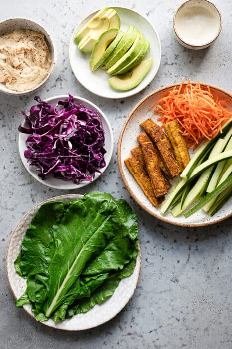 Top view of ingredients to make gluten-free collard wraps on a white plate with fresh vegetables on the side