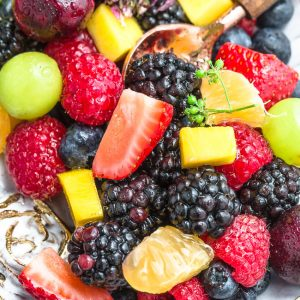 Close-up view of rainbow fruit salad in an oval platter with a spoon