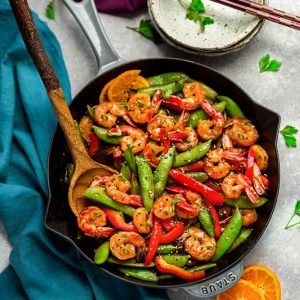Garlic Shrimp Stir-Fry – an easy 30 minute one pan recipe perfect for busy weeknights. Tender and juicy shrimp sauteed with crunchy snap peas and red bell peppers coated in a delicious sweet and savory Asian-inspired sauce better than the local Chinese restaurant takeout. Best of all, paleo, gluten free and substitution suggestions for low carb.
