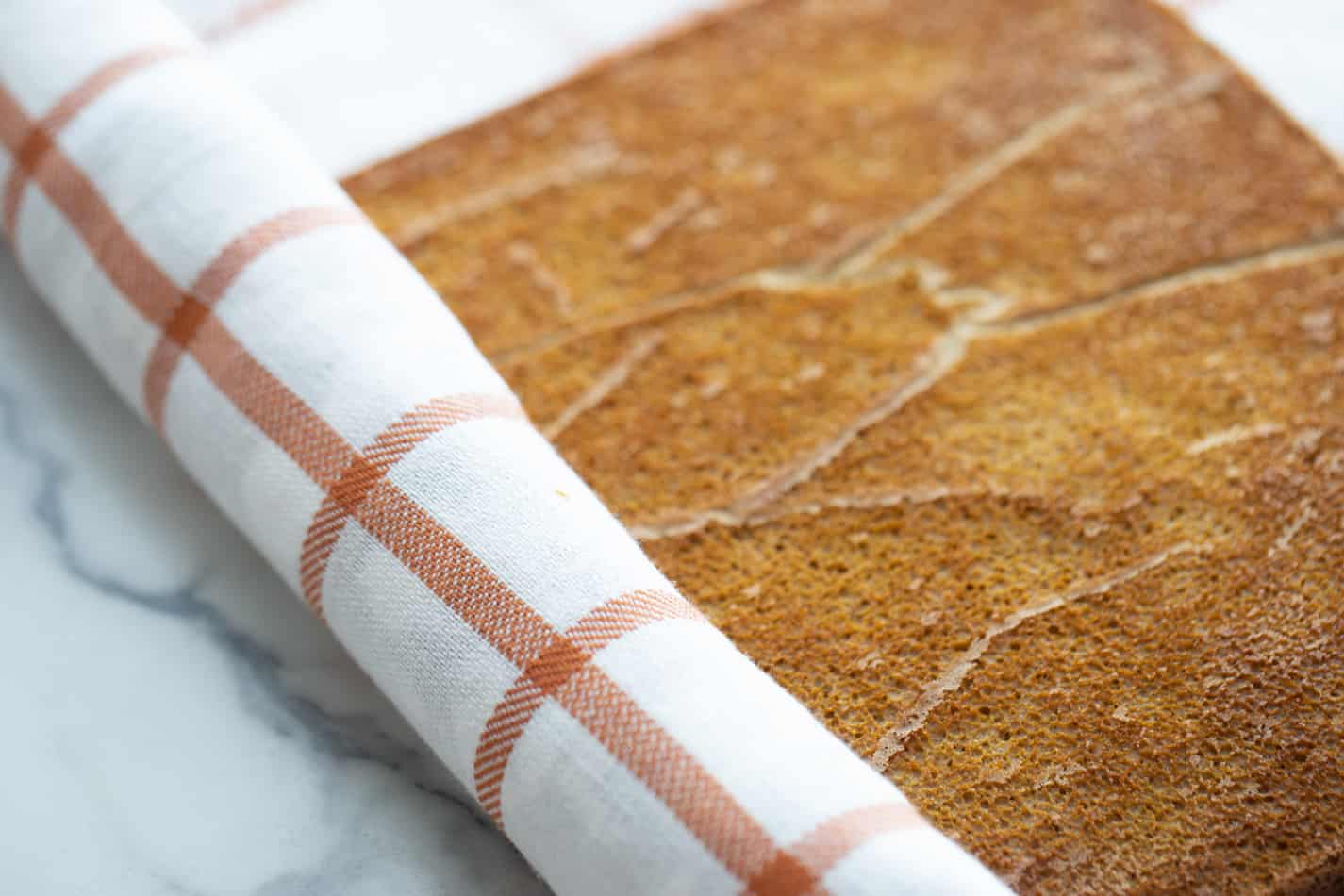 Pumpkin roll sponge cake partially rolled with a tea towel