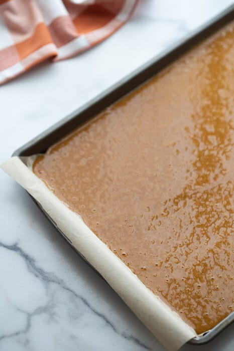 Pumpkin spice roll cake batter in a parchment-lined sheet pan