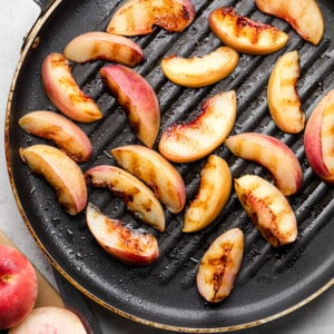 Top view of sliced grilled peaches on a grill pan