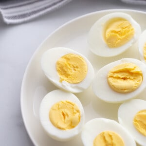 Unseasoned Hard Boiled Egg Halves on a White Plate in Front of a Cloth Napkin
