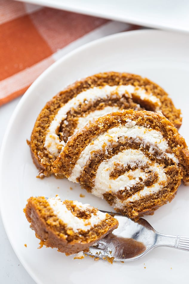 Two slices of Pumpkin Roll on a plate with a fork