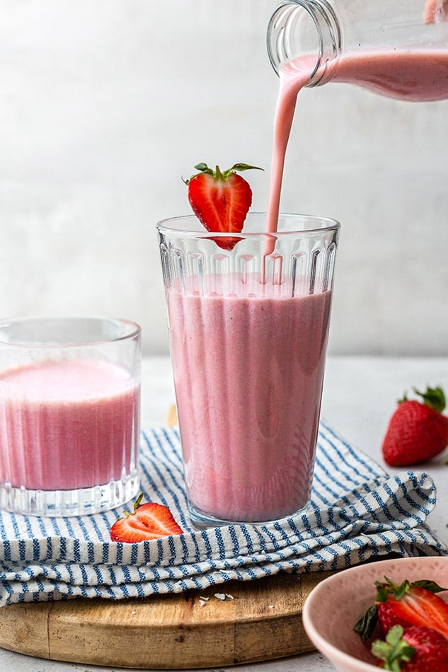 Side view of simple strawberry milkshake getting poured in a glass