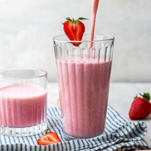 Side view of healthy strawberry smoothie getting poured in a glass