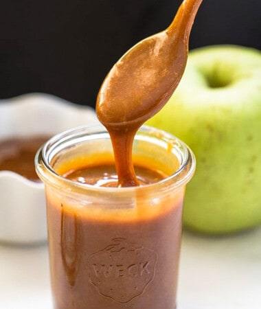 Side shot of a jar full of easy caramel sauce with a spoonful