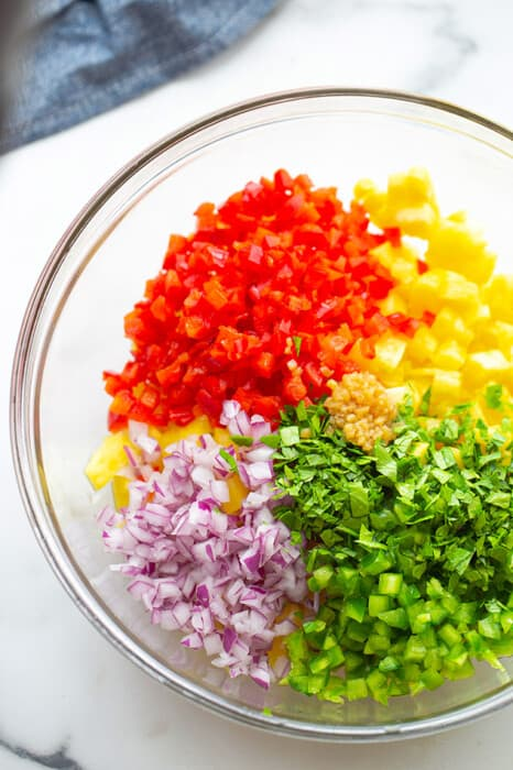 A clear mixing bowl filled with ingredients to make the pineapple salsa