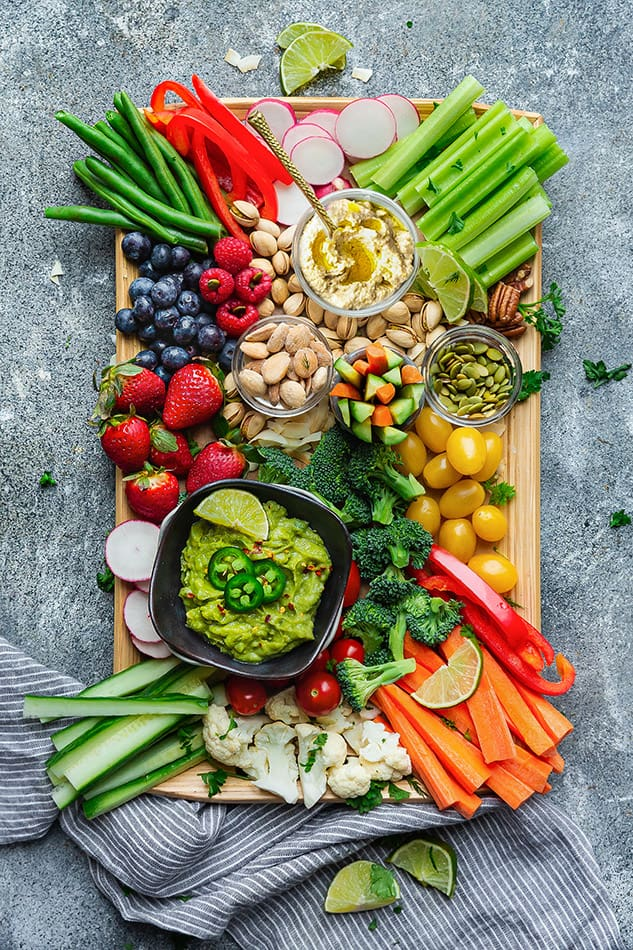 Overhead view of a veggie and fruit board with dipping sauces and nuts