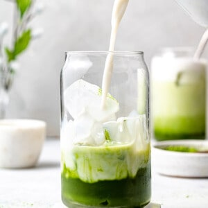 Side angle of one iced matcha in a glass and a jug of milk pouring milk into the glass
