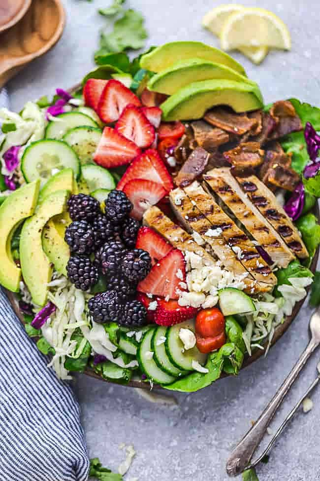 Close-up view of a loaded grilled chicken salad with berries in a bowl