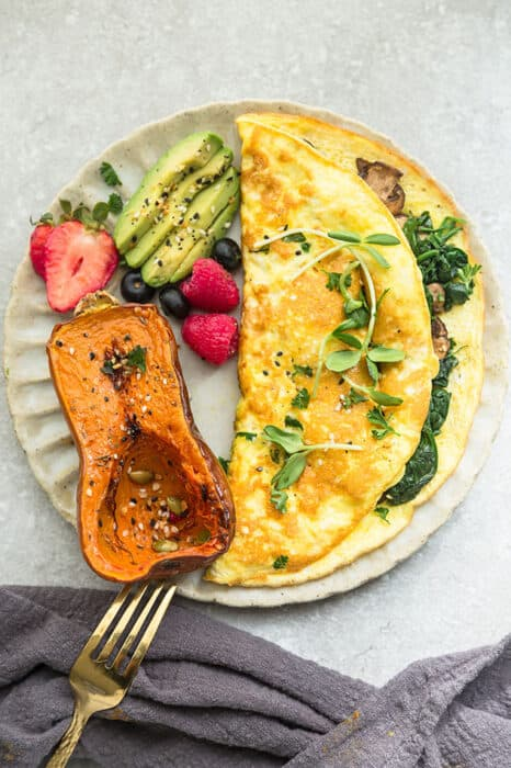 Top view of easy omelette with avocado, berries and honey nut squash on a grey plate on a a grey background with a gold fork