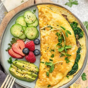 Top view of easy omelette with avocado, berries and cucumber on a grey plate on a a grey background with a gold fork