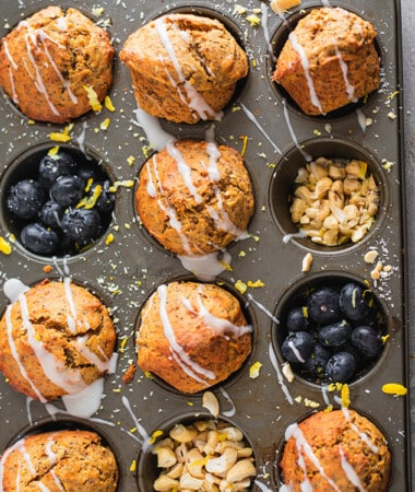 Eight Glazed Lemon Poppyseed Muffins in a muffin pan with blueberries