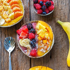 Top view of an easy mango smoothie recipe in a white bowl topped with fresh berries and a spoon