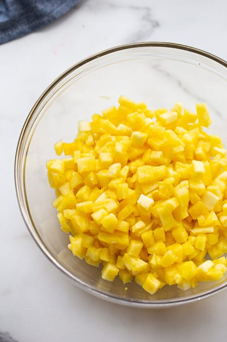 A clear mixing bowl filled with diced pineapple