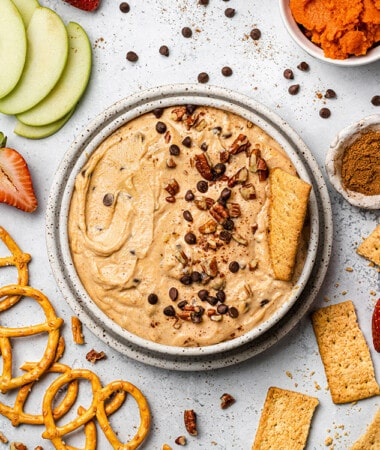 Overhead view of pumpkin dip in a bowl with mini chocolate chips, chopped nuts, and a cracker