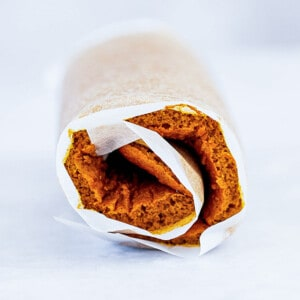 Side view of a rolled up pumpkin roll in parchment paper