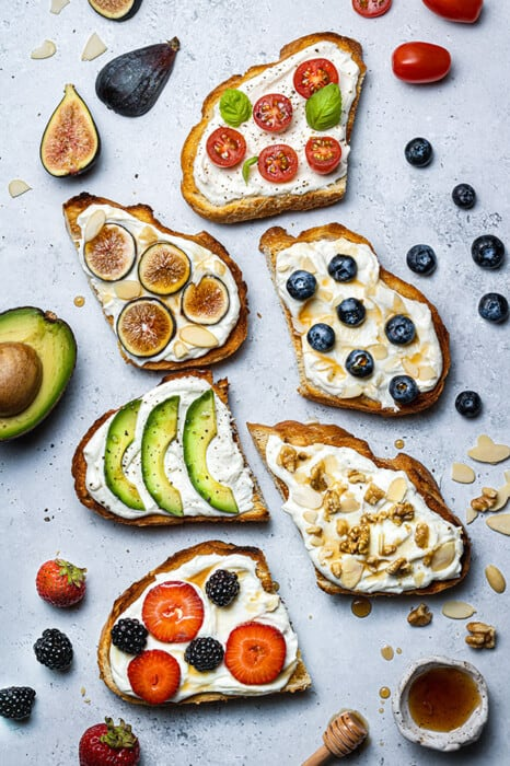 Six Whipped Ricotta Toasts on a grey background with different toppings