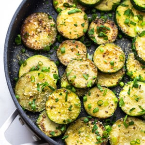 Top view of sautéed zucchini with fresh herbs in a large nonstick pan