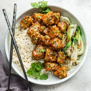 Crispy teriyaki tofu in a bowl with a side of bok choy and cauliflower rice with chopsticks