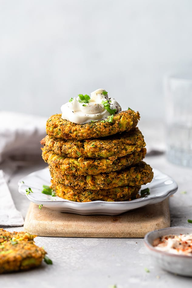 Far side view of a stack of five vegan broccoli fritters on a white plate with coconut cream