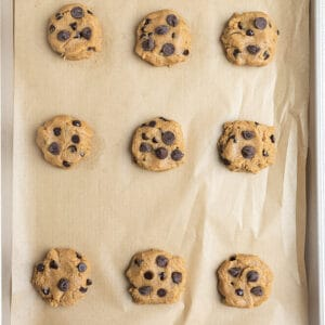 Top view of nine unbaked gluten free chocolate chip cookies on a parchment paper on a baking sheet