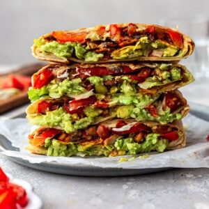 A stack of four vegan crunchwrap halves on a plate