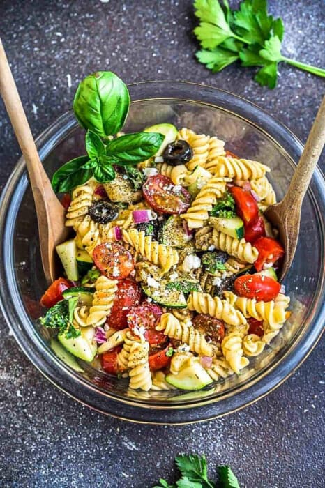 Top view of a mixing bowl with spoons of an Easy Summer Pasta Salad