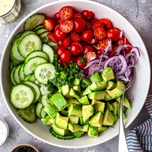 A bowl of cucumbers, cherry tomatoes, red onion and avocado in a white bowl
