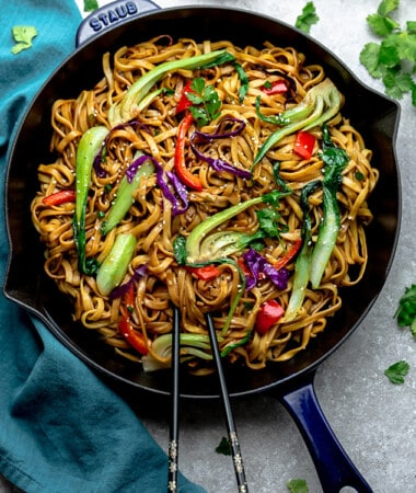 Top view of vegetable lo mein in a blue skillet with chopsticks