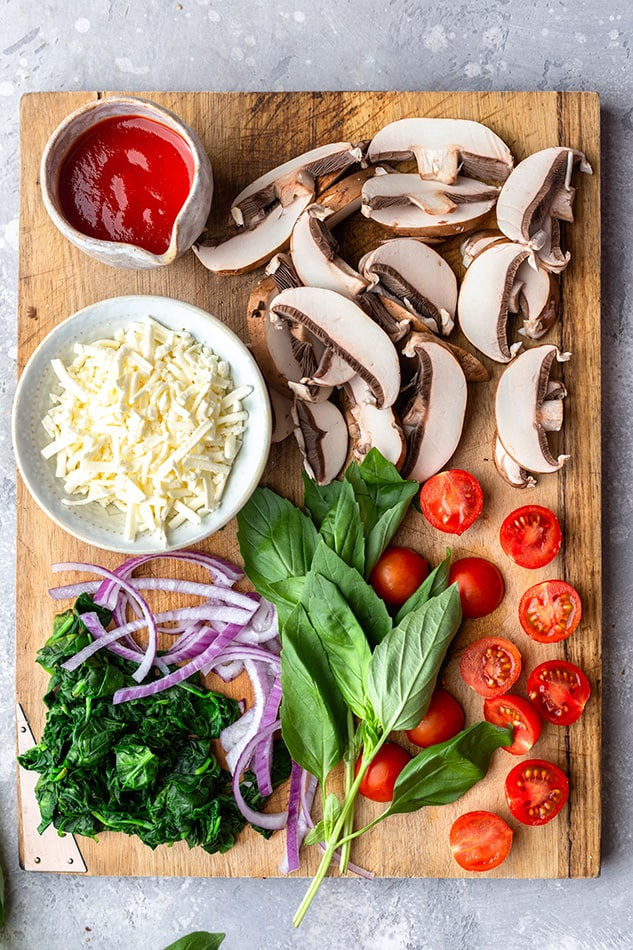 Top view of ingredients on a wooden cutting board to make vegetable pizza