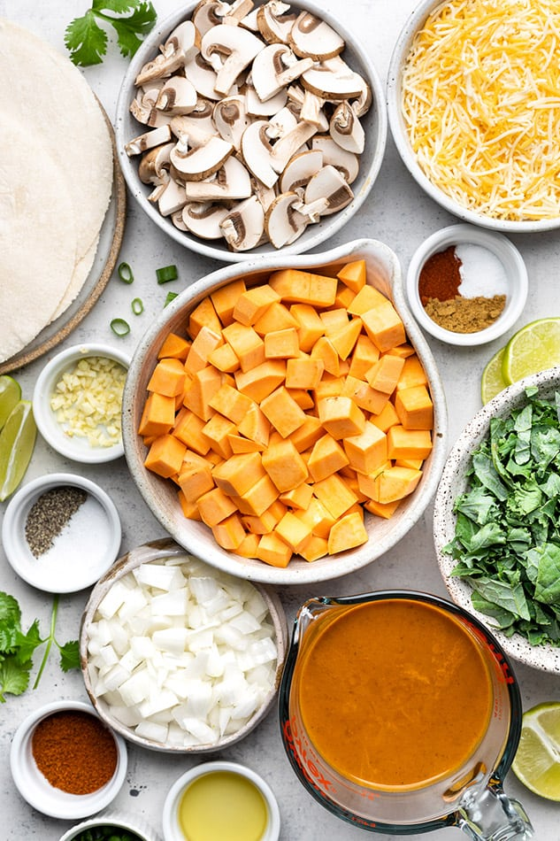 Overhead view of ingredients for vegetarian enchiladas in individual bowls