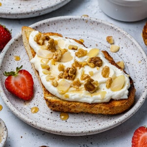 One slice of whipped ricotta toast with walnuts, sliced almonds and maple syrup on a white plate