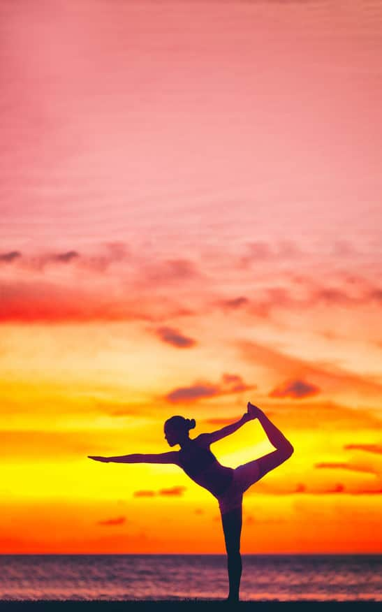 Yoga silhouette of woman stretching doing dancers pose in beautiful dusk colors at sunset on beach background. Copy space on pink sky clouds. Wellness meditation concept.