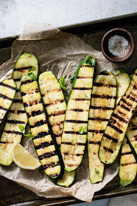 Top view of grilled zucchini slices on a parchment paper on a baking sheet