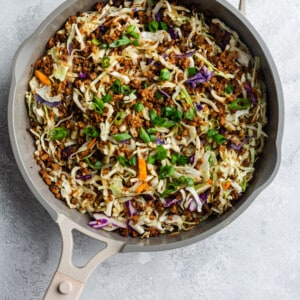 Sautéed cabbage slaw with ground meat in a grey pan
