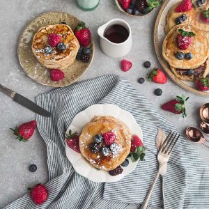 Eggless pancakes on a plate with strawberries, raspberries, blackberries and blueberries