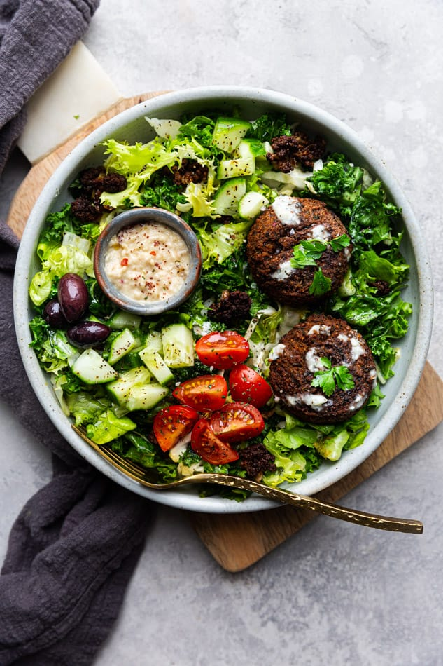 Falafel Salad in a white bowl with a gold fork